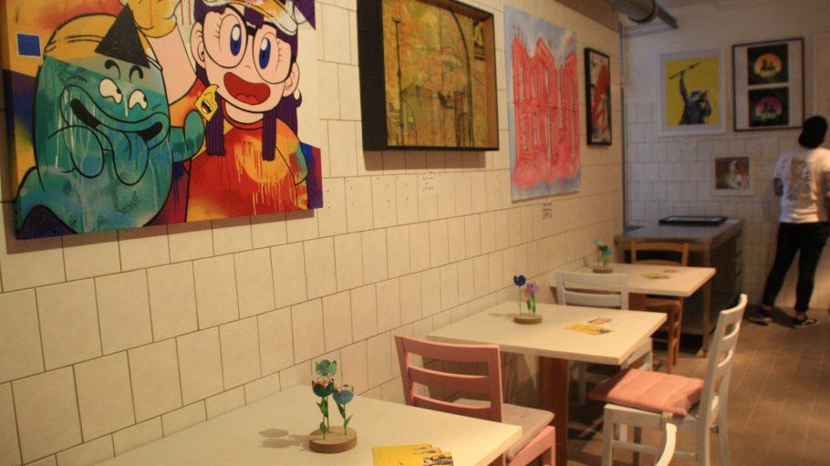 Bilder an der Wand und Tische mit Blumendeko