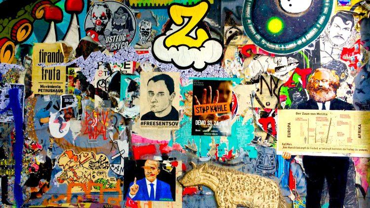 Abschnitt einer Hausfasse, auf der sich bunte Plakate, Sticker und Graffitis befinden.