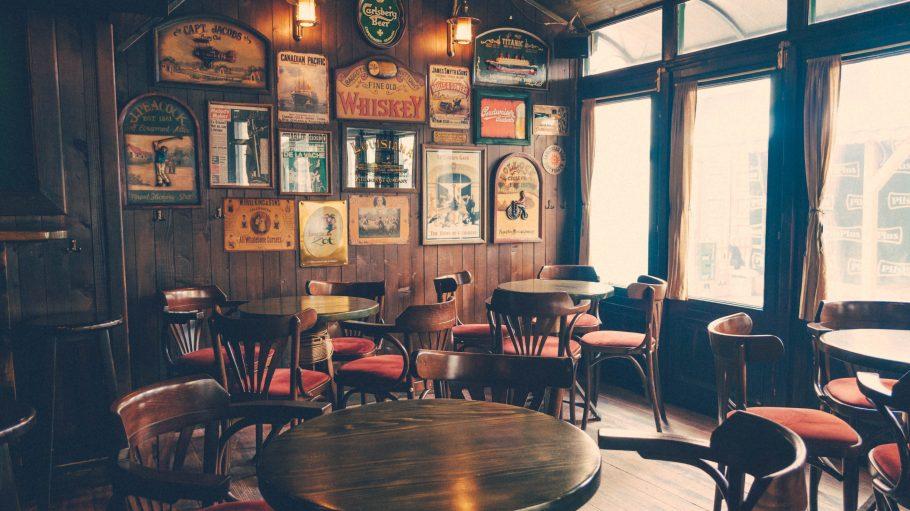Der Innenraum eines Pubs mit holzverkleideter Wand und Blechschildern an der Wand. Außerdem stehen dunkle Holztische und Holzstühle mit roten Sitzpolstern im Raum.