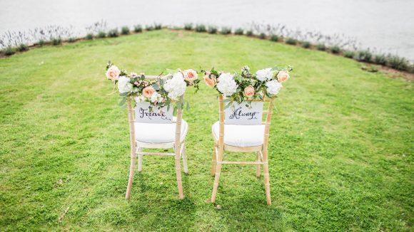 """Zwei Stühle für eine Trauung stehen vor einem See. Auf der Lehne steht einmal """"Forever"""" und einmal """"Always"""""""