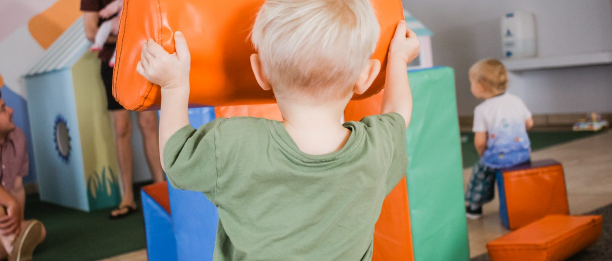 Ein Junge hält einen großen Bauklotz aus Stoff in der Hand