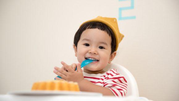 Kleiner Junge mit Löffel im Mund vor seinem Geburtstagskuchen