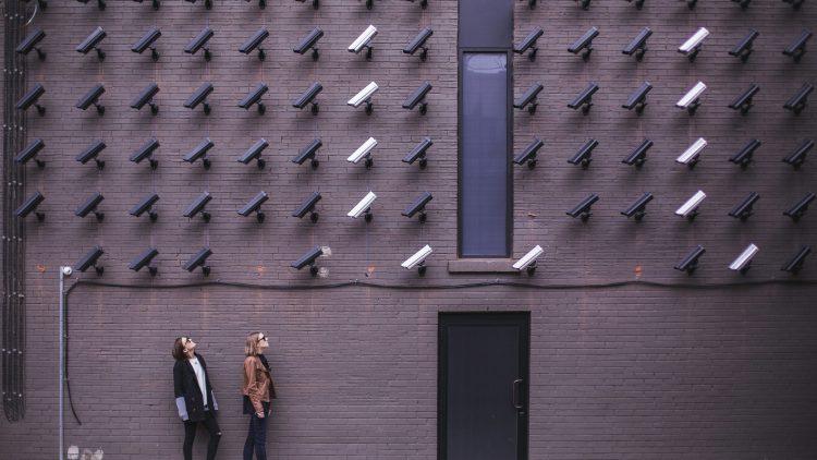 Zwei Frauen mit Sonnenbrillen stehen vor einer Wand mit vielen Überwachungskameras in Schwarz und Weiß.