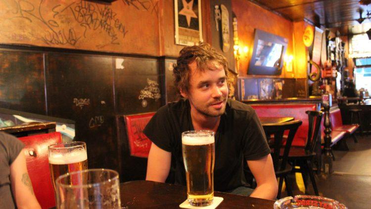 Der Schlagzeuger Max vors einem Bier beim Zuhören.
