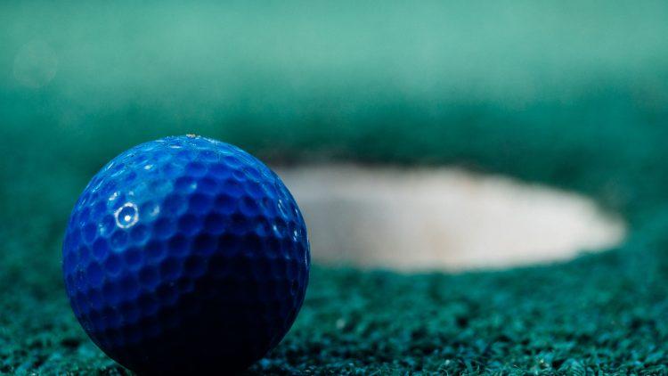 Minigolfball in Blau auf grünem Rasen vor Loch