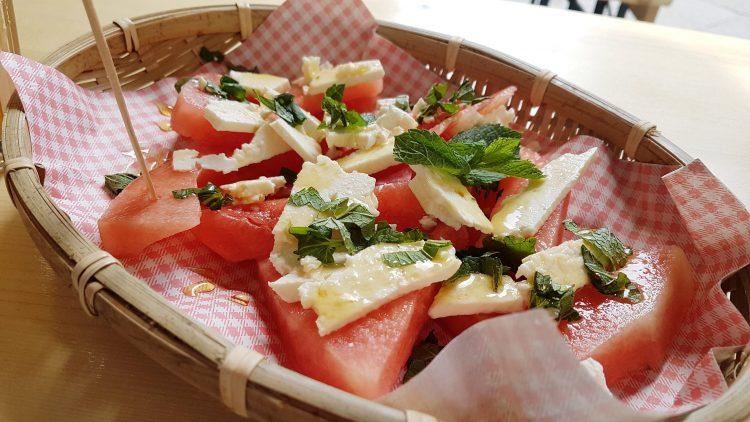 Melone mit Feta, Minze und Honig im Bastkörbchen.