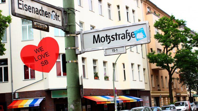 Die Straßenschilder Motzstraße/ Eisenacher Straße mit einer Bar im Hintergrund, die eine Bunte Markise hat