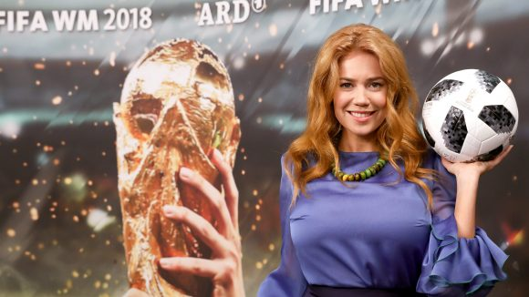 Palina Rojinski posiert als neue Fußballreporterin für die ARD vor einem WM-Plakat