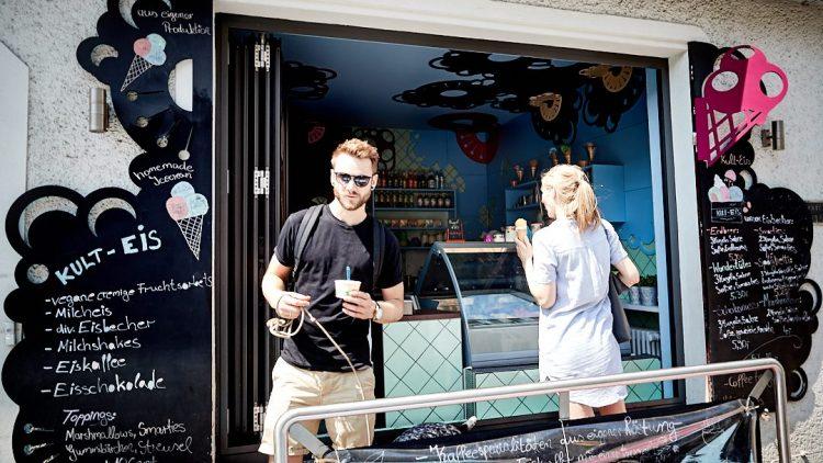 Roman Lob steht mit einem Eisbecher vor der Theke der Eisdiele Kult-Eis in Berlin. Im Hintergrund bestellt eine Frau Eis.