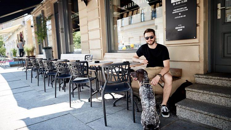 Roman Lob sitzt vor dem Café Röststätte in MItte. Vor ihm sitzt deine Deutsche Kurzhaar Jagdhündin Heidi. Sie hat einen braunen Kop und braun-weiß geflecktes, kurzes Fell.