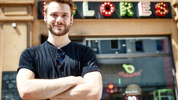 Roman Lob lächelt mit verschränkten Armen in die Kamera. Im Hintergrund: Dolores Restaurant.
