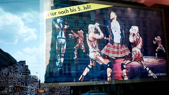 Szene aus The One im Fenster vom Friedrichstadt-Palast: Roman Lob kniet in seinem Kostüm mit Lederjacke und Schottenrock auf den Knien von zwei Artisten