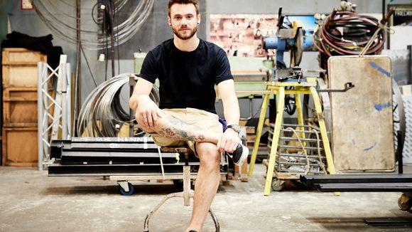 Roman Lob sitzt auf einem alten Handwerker-Hocker, ein Bein auf dem Boden, das andere auf dem Knie. Er trägt kurze Hosen und ein schwarzes Shirt. Ein buntes Tattoo auf dem Schienbein ist zu sehen. Im Hintergrund stehen eine Säge und Material vom Bühnenbau.