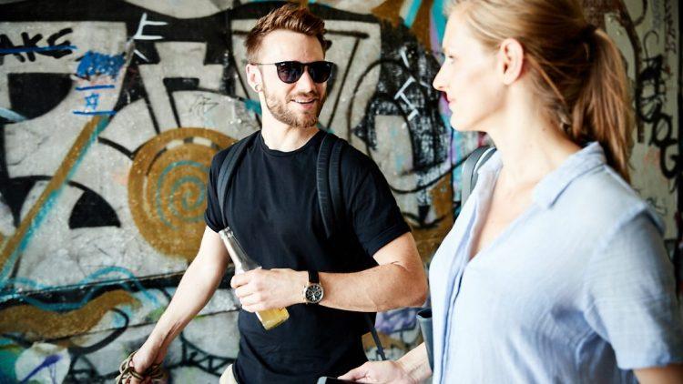 Roman Lob und eine blonde Journalistin laufen an einer mit Graffiti besprühten Wand entlang.