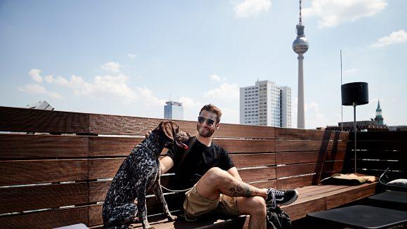 Roman Lob sitzt auf der Dachterrasse vom amano Hotel in Mitte auf einer Sitzbank mit hoher Rückenlehne aus dunklem Holz. Im Hintergrund sieht man den Fernsehturm.