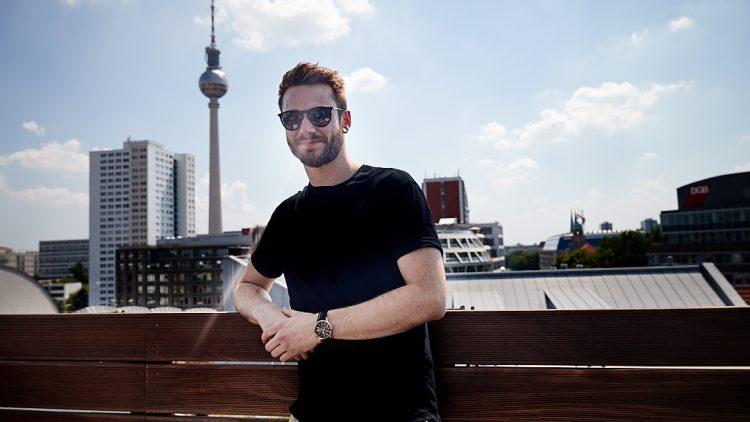 Roman Lob lehnt an einem Holzgeländer. Im Hintergrund sind Dächer, das Park Inn Hotel und der Fernsehturm zu sehen.