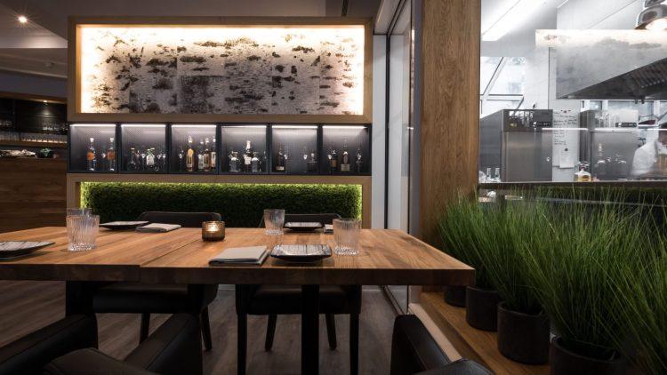 Tisch mit Stühlen und schöner grüner Deko im Restaurant SAVU