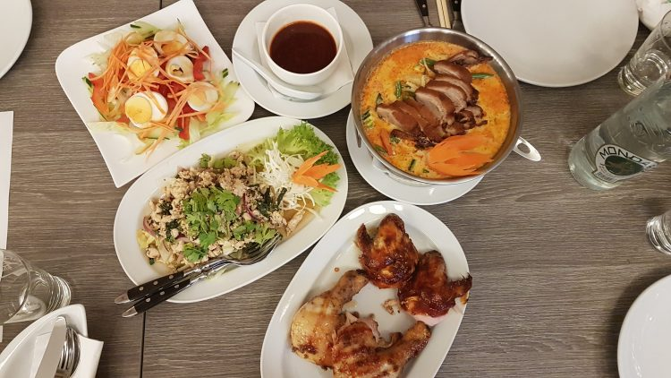 Hühnchen, Salate und ein Thaicurry stehen auf dem Tisch.