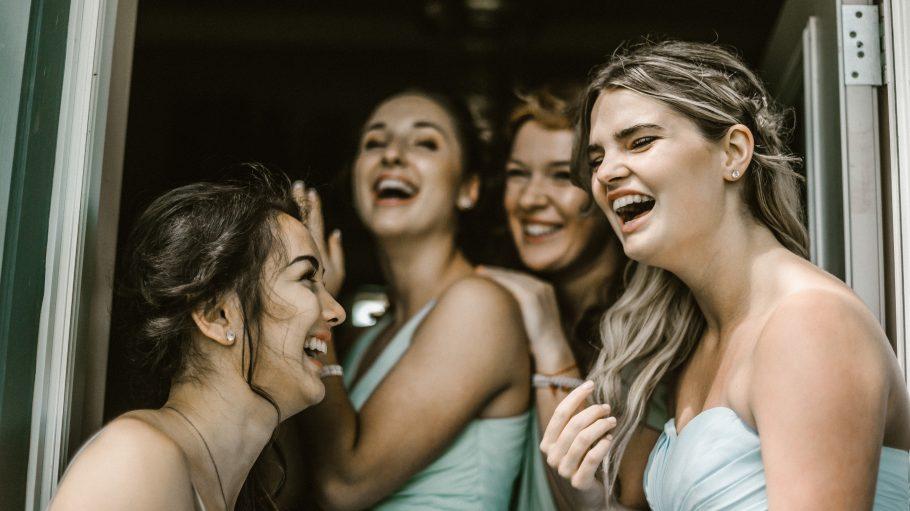 Frauen in hellen kleidern lachen gemeinsam
