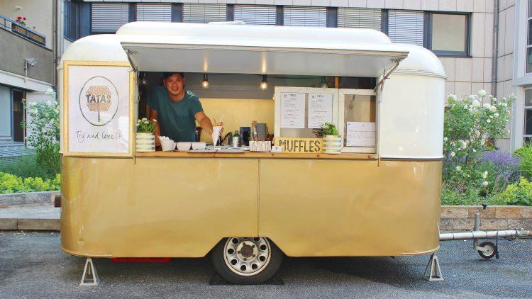 Verkäufer reicht Waffel in Tüte aus Food Truck