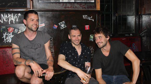 Die drei Bandmitglieder von Vizediktator sitzen in einer Reihe.