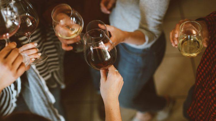Einige Leute stoßen Abends mit Wein an