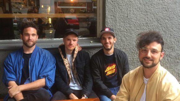 Die Band sitzt an einem Holztisch vor der Bar.