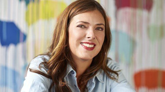 Die DaWanda Gründerin Claudia Helmig hat braune Haare lange Gaare und braune Augen, sie sitzt in einer hellen Bluse und lächelnd vor einer bunt bemalten Wand.
