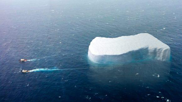 Zwei Schiffe ziehen einen riesigen Eisberg.