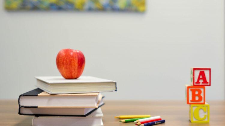 Bücher und ein Apfel in einer Schule.
