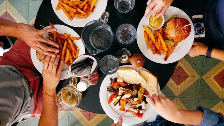 Menschen essen gemeinsam an einem Tisch Burger und Pommes