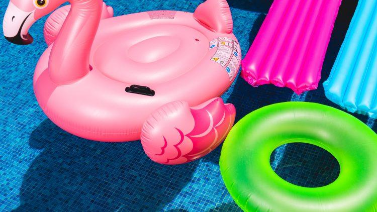 Bunte Luftmatrazen in pink und blau, ein neongrüner Schwimmring und ein pinker Schwimm-Flamingo schwimmen in einem Pool mit blauen Kacheln.