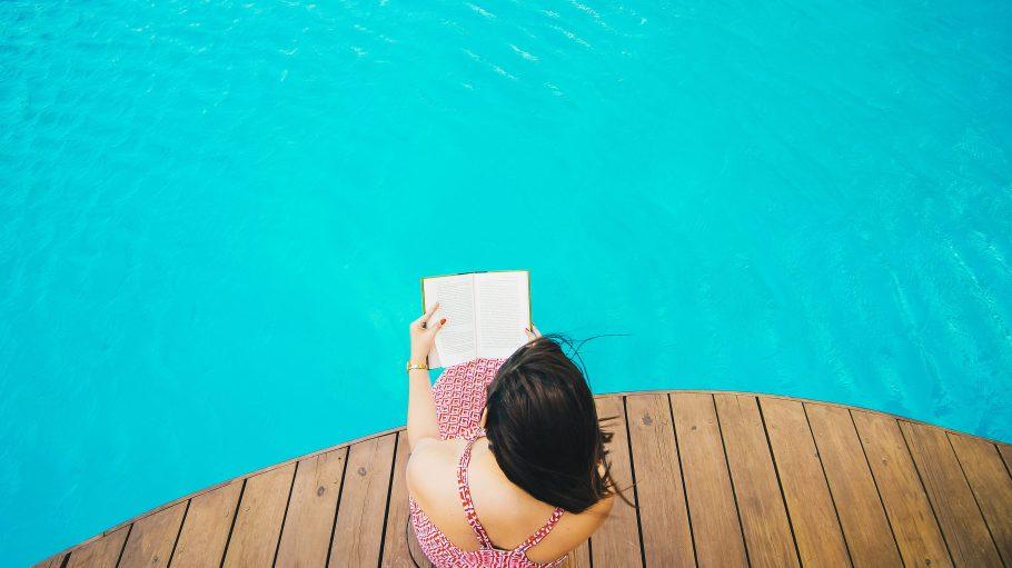 Eine Frau in einem roten Kleid sitzt auf einem Holzsteg am Pool und liest ein Buch, fotografiert von oben