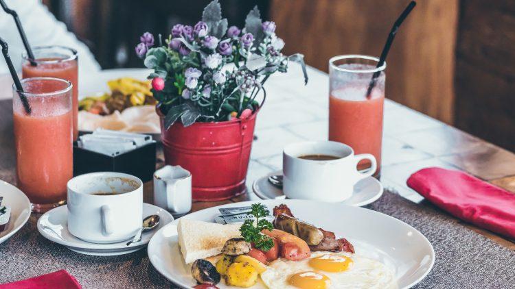 Tisch mit Teller mit Speigelei und Würstchen, dazu Kaffee und Saft und ein Topf mit Bluemen
