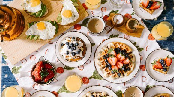 Brot mit Avocado und Spiegelei und Waffeln mit Erdbeeren und Blaubeeren sind neben Saft und Kaffee auf einem Frühstückstisch zu sehen, der von oben fotografiert wurde.
