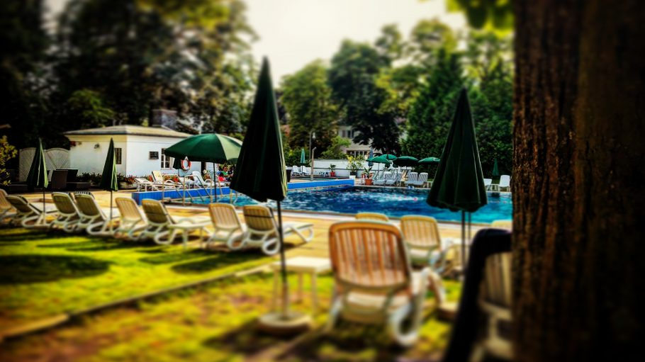 Swimming-Pool mit Liegestühlen im Garten mit Bäumen