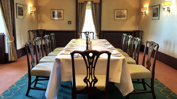 Gedeckte Tafel mit zehn Stühlen in mit Teppich ausgelegtem Zimmer des International Club Berlin