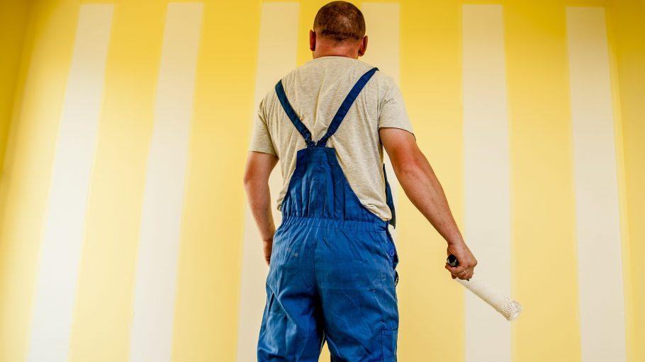Ein Hausmeister steht vor einer gelben Wand und streicht.
