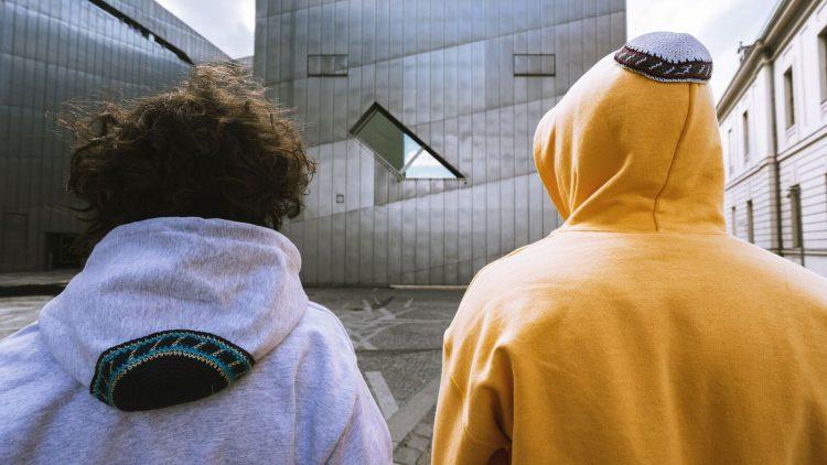 Zwei Männer mit dem Rücken zu uns mit einem grauen und gelben Hoodie mit Kippa auf der Kapuze.