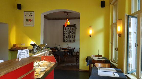 Die Inneneinrichtung des Capperi mit gelber Wand, roter Theke und blauen Tischtüchern.