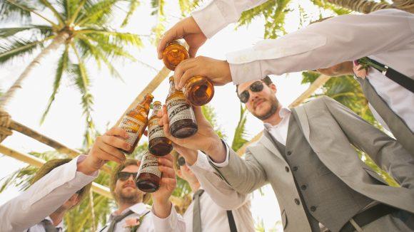 Fünf Herren in Anzügen unter Palmen prosten sich mit Bierflaschen zu