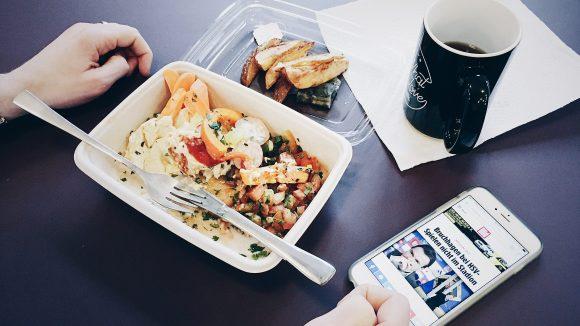 Eine Lunchbox auf dem Tisch mit Kaffee und Handy Nebendran