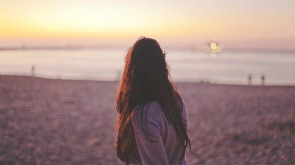 Junge Frau abends am Strand schaut aufs Meer