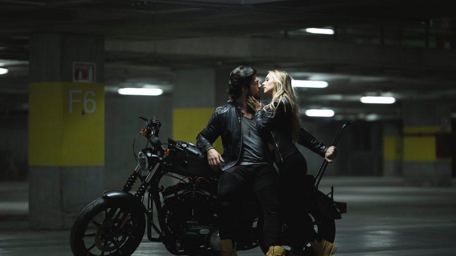 Eine Frau und ein Mann küssen sich auf einem Motorrad im Parkhaus