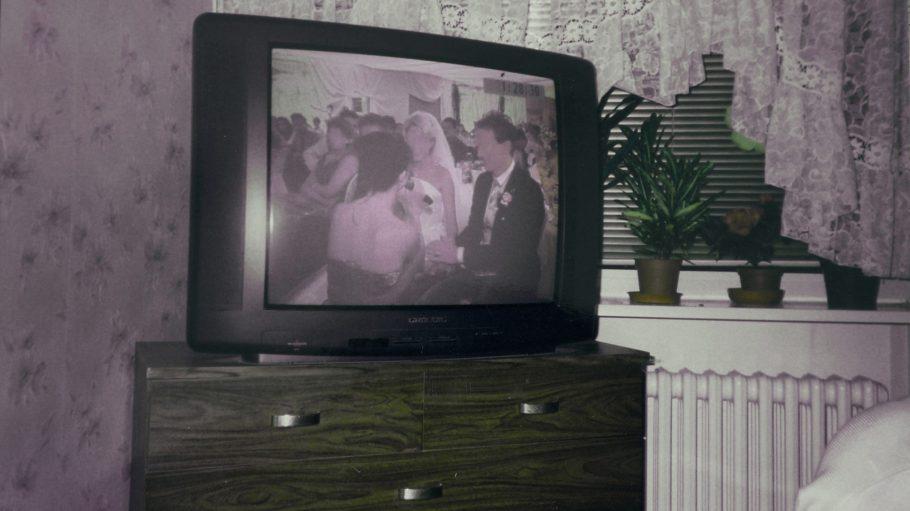 Fernseher, auf dem eine Hochzeit zu sehen ist, auf einem Schränkchen aus dunklem Holz. Im Hintergrund bunte Tapete, Spitzengadine und weiße Heizung
