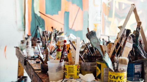 Viele Pinsel in Dosen und Bechern auf einer alten Werkbank mit Farbresten, im Hintergrund ist ein buntes Bild leicht evrschwommen zu erkennen.