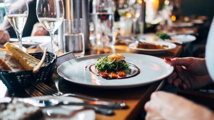 Teller mit Lachs und Salat an gedecktem Tisch