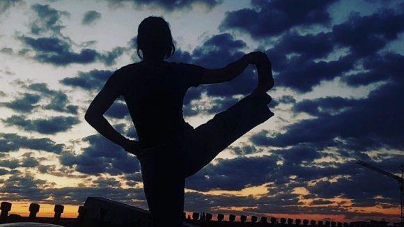 Eine Frau übt Yoga auf einem Dach im Wedding beim Sonnenuntergang.