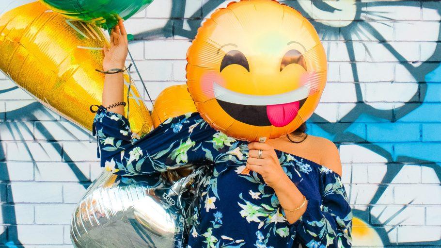 Frau mit lachendem Emoji-Luftballon vor dem Gesicht.