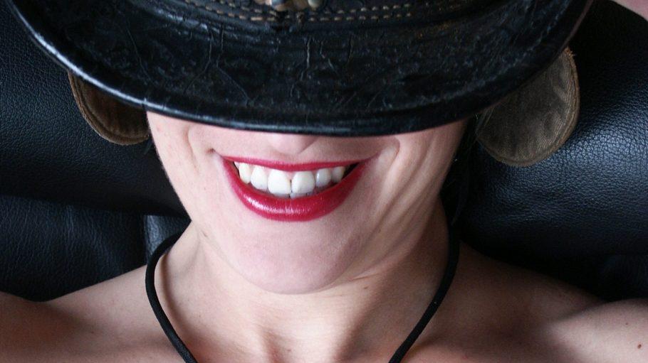 Gesicht einer lächelnden Frau, die ihre Augen mit einem Hut verdeckt